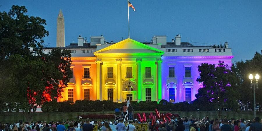 In this Friday, June 26, 2015 file photo, people gather in Lafayette Park to see the White House illuminated with rainbow colors in commemoration of the Supreme Court's ruling to legalize same-sex marriage in Washington. The Trump administration Friday, June 12, 2020, finalized a regulation that overturns Obama-era protections for transgender people against sex discrimination in health care.