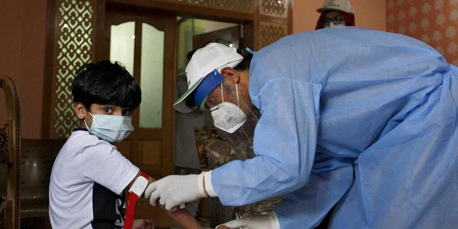 A health worker takes blood sample of a boy during door-to-door testing and screening facility for the coronavirus in Pakistan. (Photo| AP)