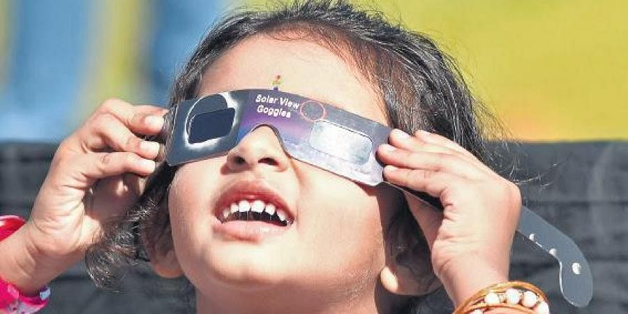 A child watches the annular solar eclipse using special goggles.