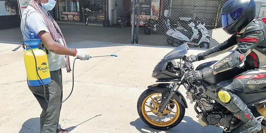 A worker disinfects one of the participant's bike at MMRT in Irungattukottai, Chennai, on Sunday. According to MMRT official, a total of 24 bikers were present during the session