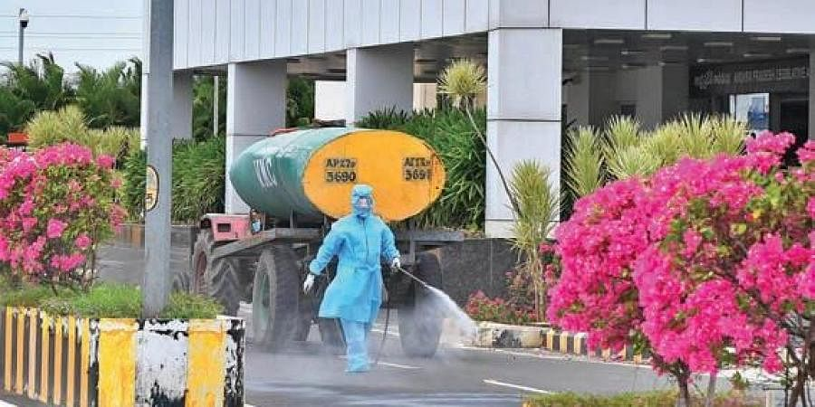 A worker sprays disinfectant in the Assembly premises a day ahead of the Budget session of the Assembly, at the Secretariat in Velagapudi on Monday
