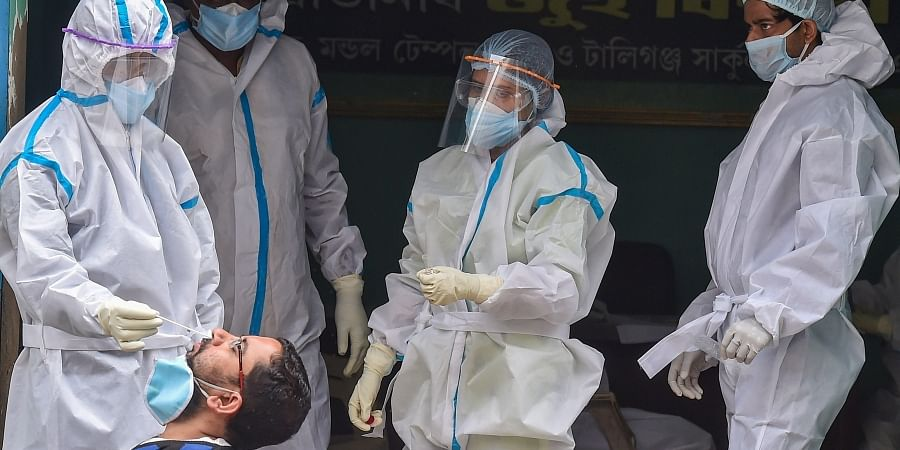 A health worker collects swab sample of a person for COVID-19 test at a center during the nationwide lockdown in Kolkata Wednesday June 17 2020.