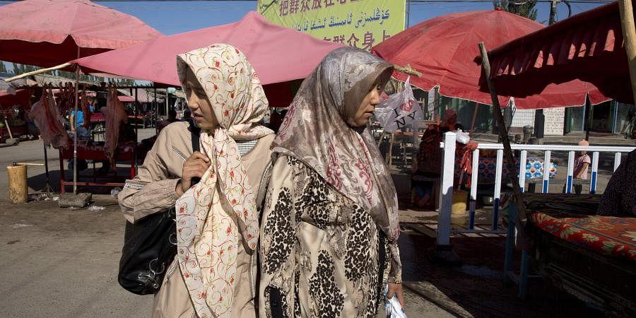 Uighur Muslim women visit a market in Alaqagha in western China's Xinjiang province in July.