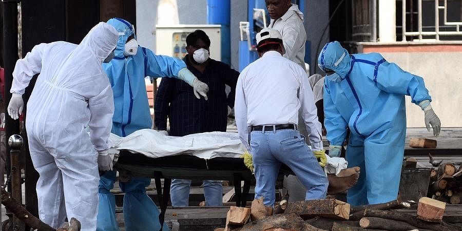 Health workers and family members in personal protective suits move the body of a man who died of Covid 19 for cremation in New Delhi on Friday May 29 2020. (Photo | Parveen Negi/EPS)