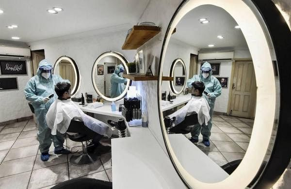 A barber wearing a PPE kit attends to a customer during the ongoing COVID-19 lockdown at Bengali Market in New Delhi on Tuesday. (Photo   PTI)