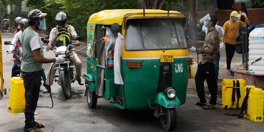 Workers spray disinfectant on an auto-rickshaw. (Photo   PTI)