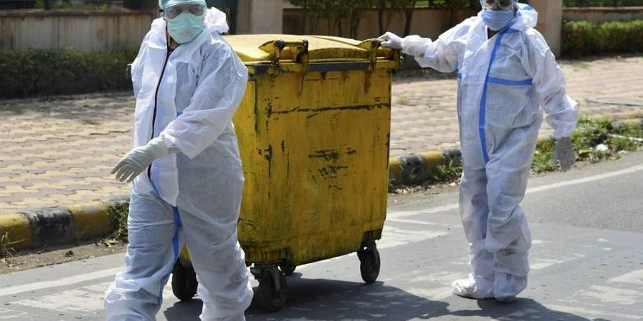 Workers in protective suits dispose COVID-19 bio-medical waste outside a hospital during the ongoing nationwide lockdown to curb the spread of coronavirus in New Delhi