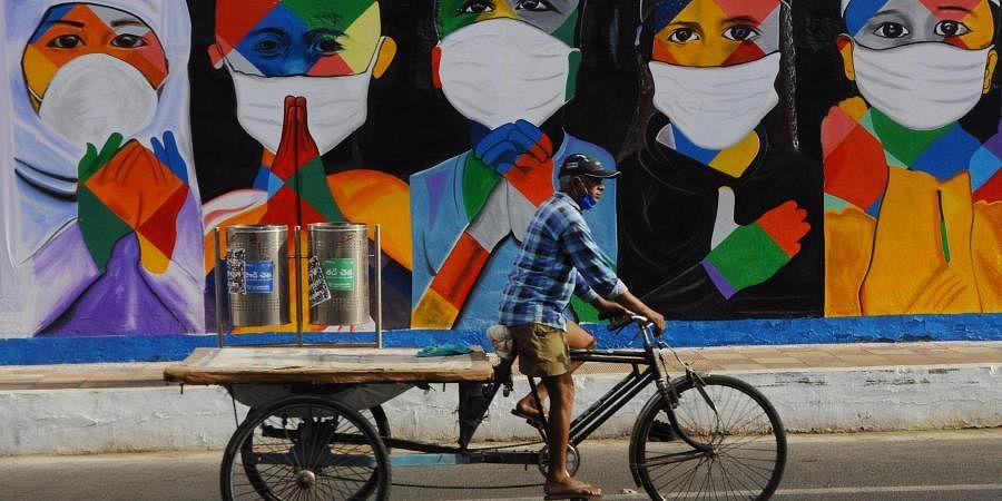 A rickshaw wala passes through a painting creating awareness on wearing face mask in Vijayawada on Monday.