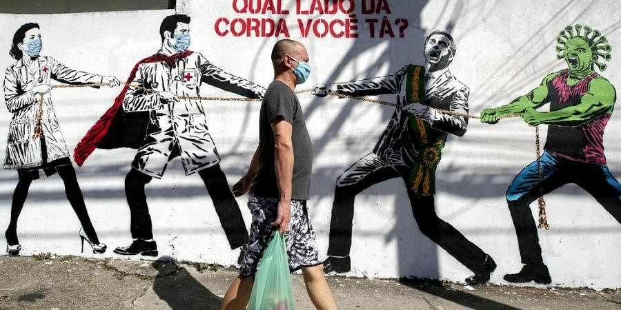 A man, wearing a protective face mask as a measure to curb the spread of the new coronavirus, walks past a mural depicting a tug-of-war between health workers and Brazil's President Jair Bolsonaro aided by a cartoon-styled coronavirus character, with a message that reads in Portuguese: 'Which side are you on?,' in Sao Paulo, Brazil, Friday, June 19, 2020.