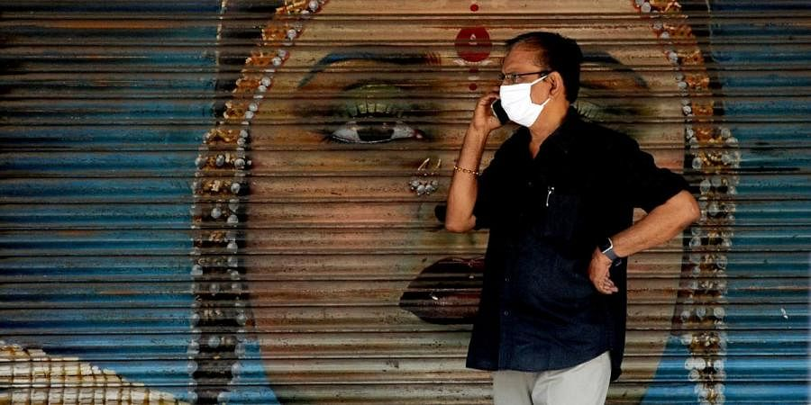 A mask-clad individual is speaking over phone in front of a jewellery shop in Kaloor on Friday