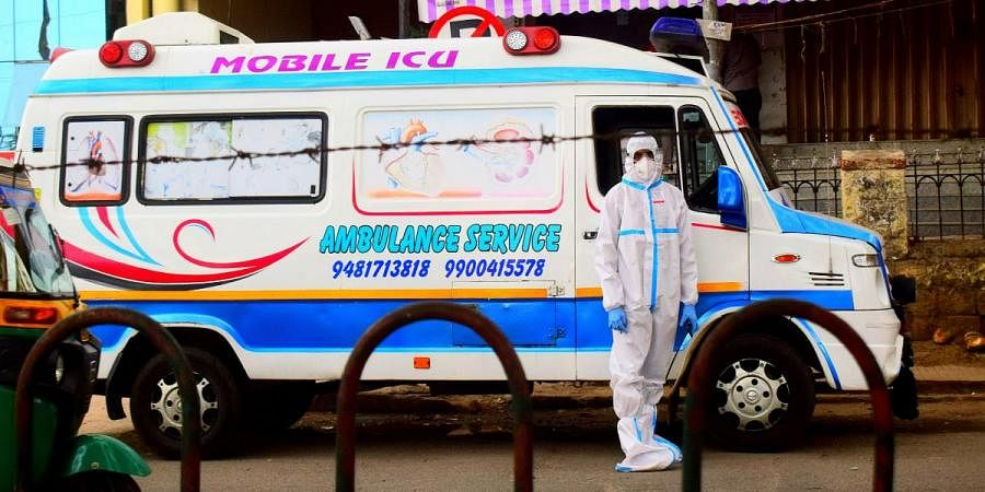 An ambulance driver wearing PPE waits near Kempegowda Bus Station in Bengaluru on Sunday