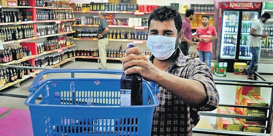 A mask-clad man buys alcohol from a Bevco outlet in Kochi before the lockdown