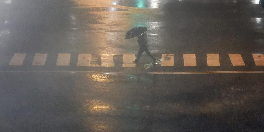 A pedestrian takes cover under an umbrella during heavy monsoon rain in Mumbai.