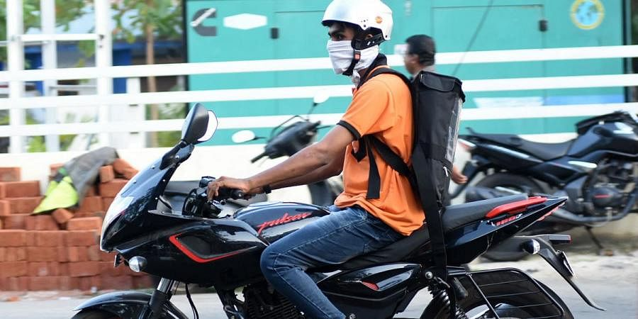 A Swiggy delivery boy wears a mask on his way  to deliver food