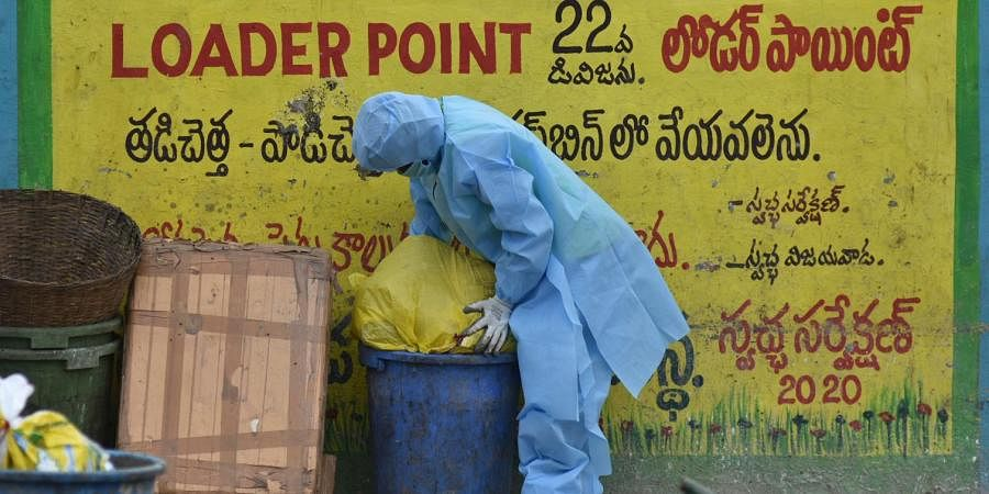 A sanitation worker putting garbage seperately collected from the houses of positive patients at Krishnalanka in Vijayawada.