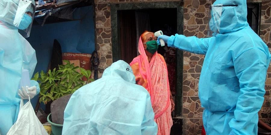 Healthcare workers wearing PPE kits check the temperature of a resident during a check-up campaign for COVID-19 in Mumbai