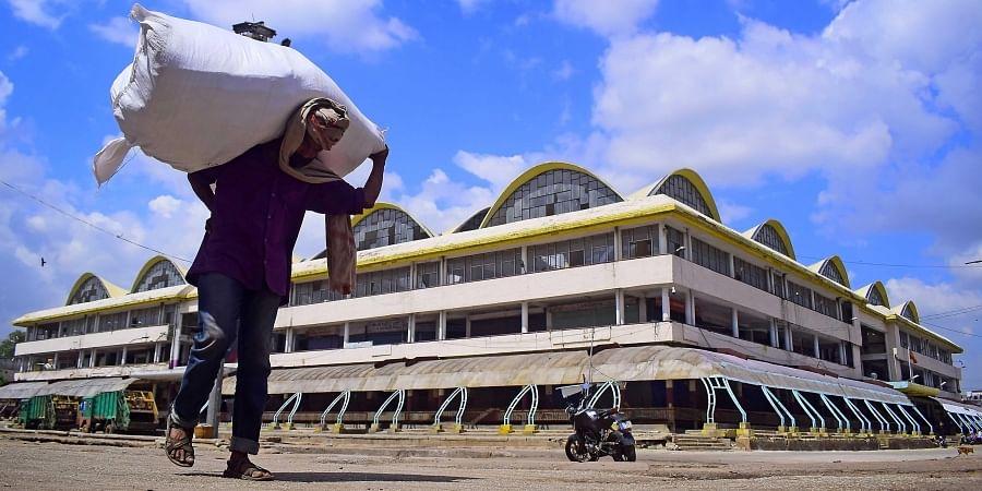 A man carrying a sack walks on an empty road opposite KR Market