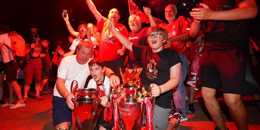 Liverpool supporters with replica Premier League and Champions League trophies as they celebrate outside of Anfield Stadium. (Photo | AP)