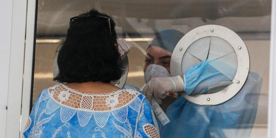 Medical staff takes a sample from a woman to test for COVID-19, at an apartment complex in Mondragone, Italy