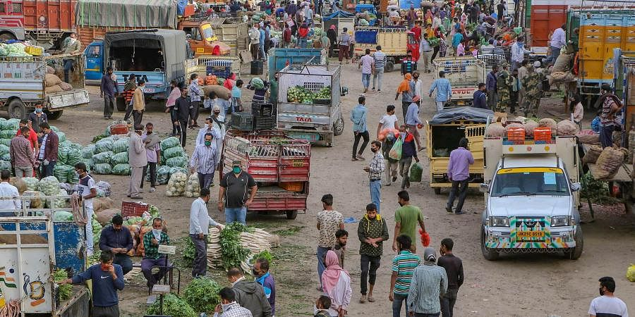 People buy vegetables at a market during a nationwide lockdown in the wake of coronavirus pandemic in Jammu.