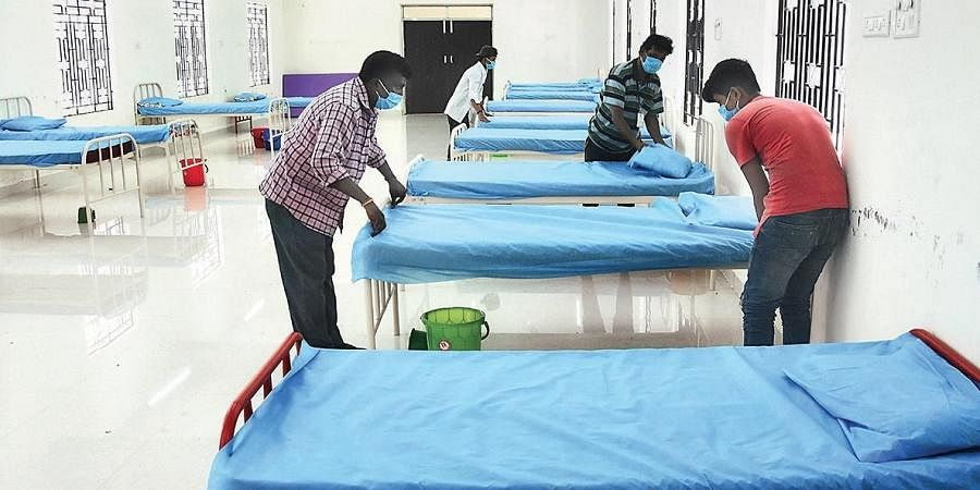 Staff setting up beds at the Covid Care Centre at Anna University.