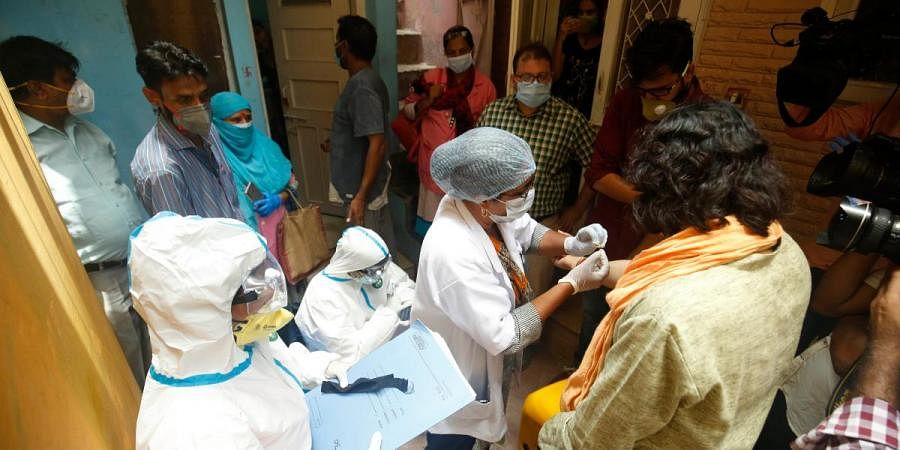 A medic takes blood samples from a resident during a door-to-door COVID-19 survey in New Delhi