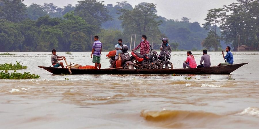 Villagers cross a flooded area on a boat following heavy monsoon rain at a village in Morigaon district Sunday June 28 2020.