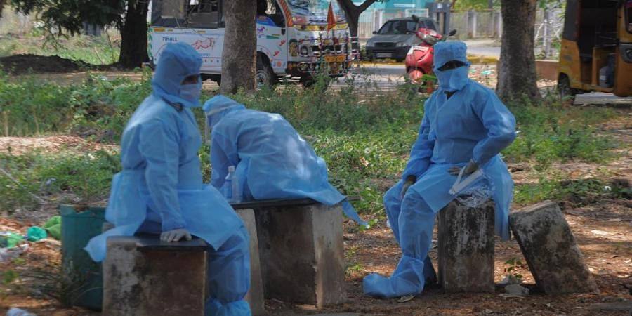 Sanitation workers, who carried a dead body waiting outside ESI hospital, while doctors conduct coronavirus test on the corpse. (Photo| Prasant Madugula, EPS)