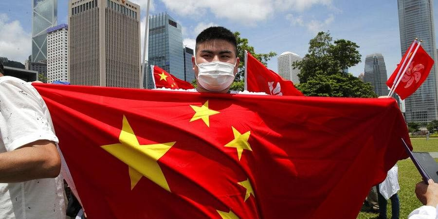 A pro-China supporter holds a Chinese national flag during a rally to celebrate the approval of a national security law for Hong Kong, in Hong Kong, Tuesday, June 30, 2020.