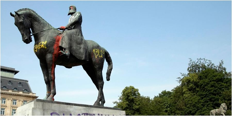 a statue of Belgium's King Leopold II is smeared with red paint and graffiti in Brussels.