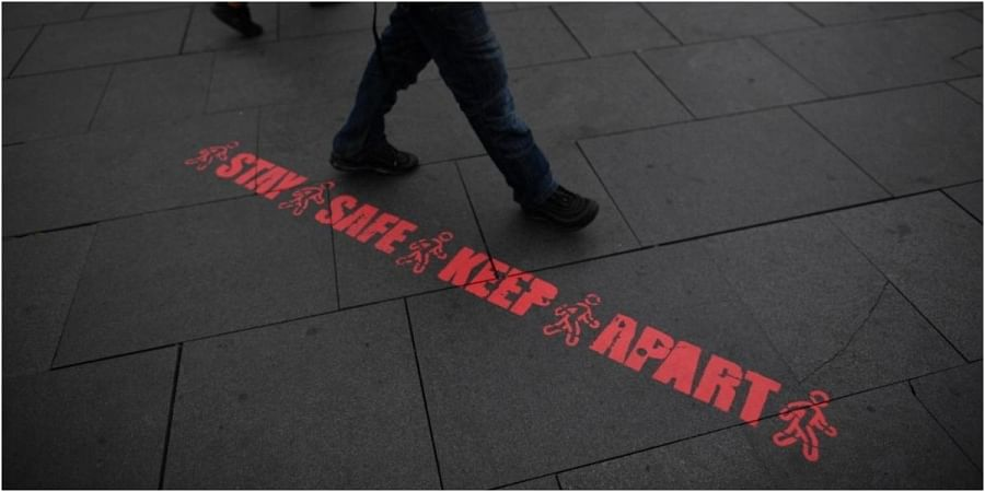 A pedestrian walks past a stencilled message reminding people to practice social distancing as a precaution against the spread of COVID-19 in the centre of Leicester, central England, on June 29, 2020.