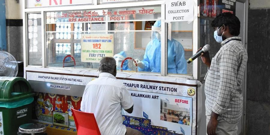Health officials collect swab samples from a passenger before boarding a train in Tirupati railway station