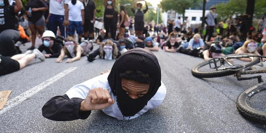 Protesters lie on a street during a demonstration Monday, June 1, 2020, in Atlanta over the death of George Floyd, who died May 25 in Minneapolis.