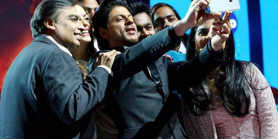Actor Shahrukh Khan takes a selfie with RIL Chairman Mukesh Ambani and his family during the launch of Reliance Jio 4G services in Mumbai.