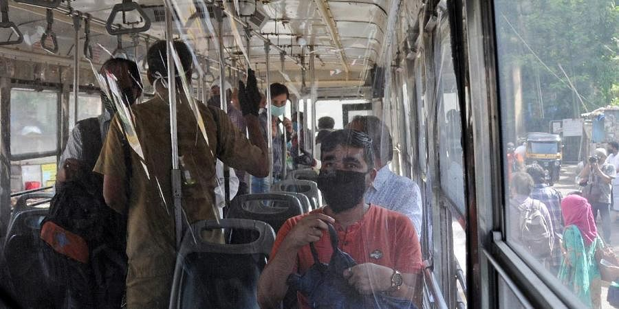 Passengers are seen seated inside the bus behind a plastic sheet as protection after easing in lockdown restriction, in Mumbai