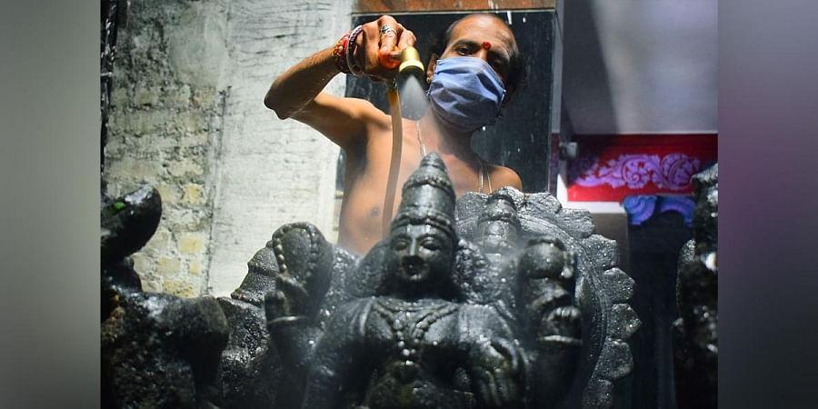A priest sanitises idols at a Lord Venkateshwara temple in Rajajinagar in Bengaluru