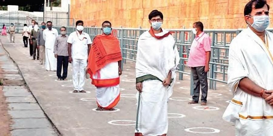 Maintaining physical distance, Srisailam temple staff stand in a queue during a trial run on Monday