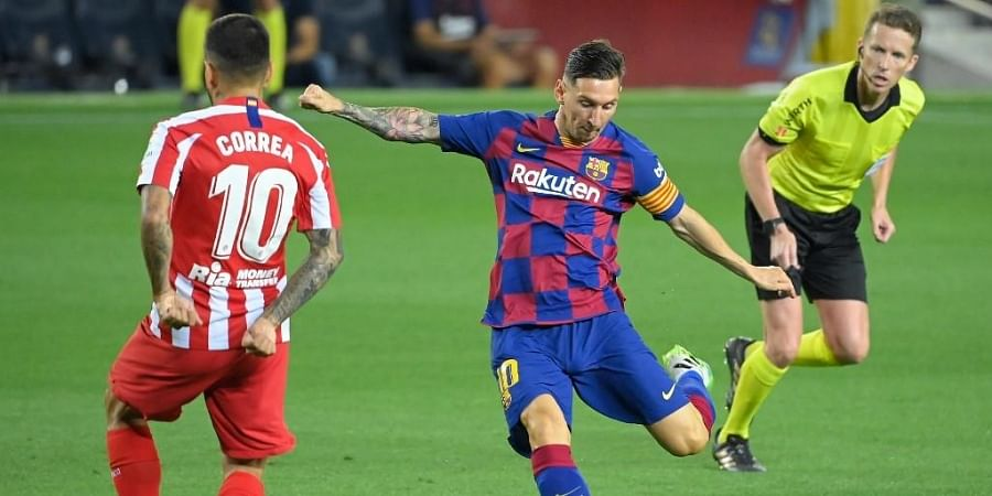 Barcelona's Argentine forward Lionel Messi (C) controls the ball next to Atletico Madrid's Argentine forward Angel Correa during the Spanish League football match. (Photo | AFP)