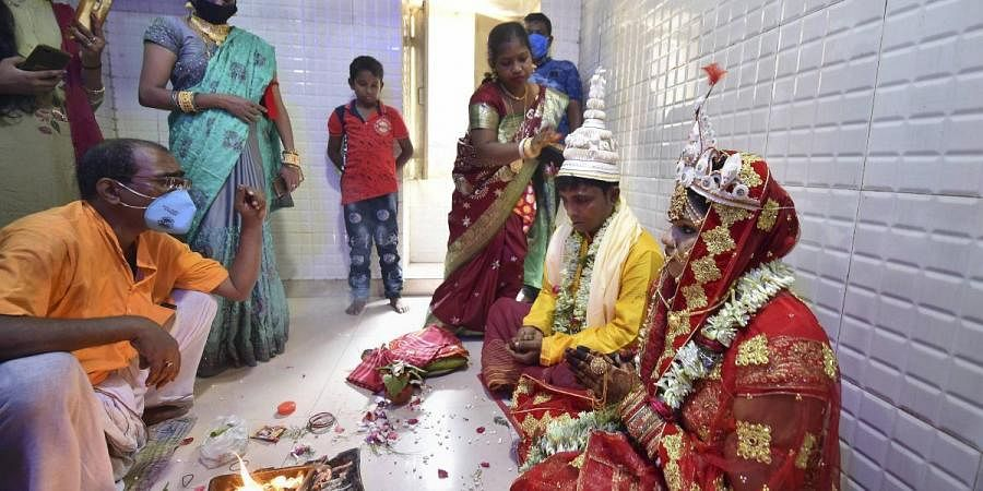 A couple take part in traditional rituals during their marriage ceremony at a priest's house near Kalighat Kali temple in Kolkata