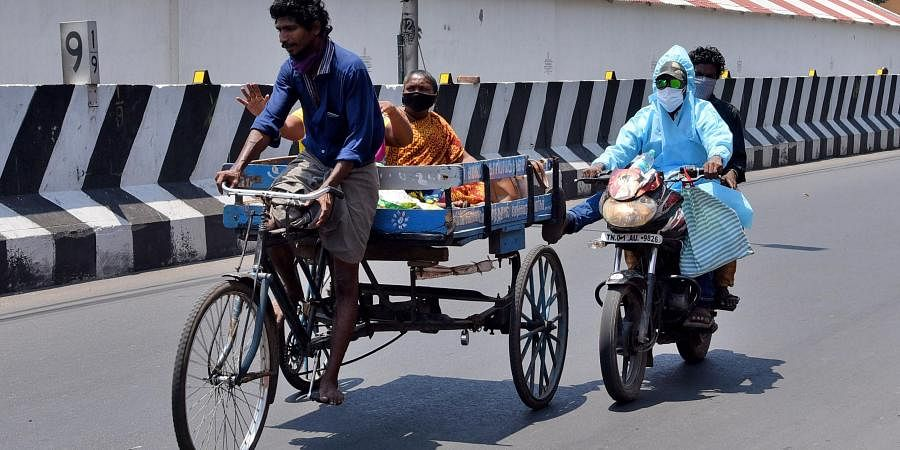 A motorist wearing PPE kit leveraging a tricycle at Periyamet