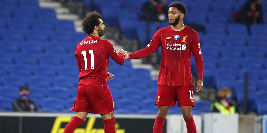 Liverpool's Mohamed Salah, left, is congratulated by teammate Joe Gomez