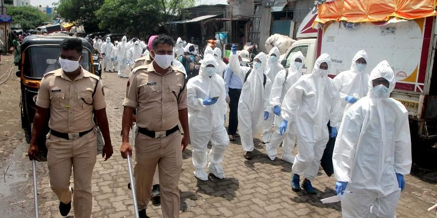 Health workers, wearing PPE, are escorted by policemen as they arrive to screen people in a slum at North Mumbai