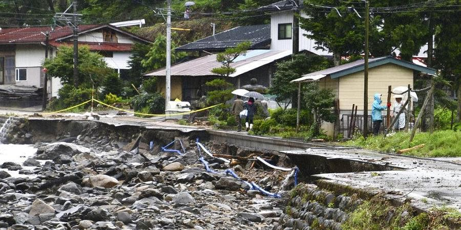 People walk on a road damaged by water following a heavy rain in Takayama, Gifu prefecture, central Japan Friday, July 10, 2020. Parts of Nagano and Gifu, including areas known for scenic mountain trails and hot springs, have been flooded by massive downpours that have lasted for nearly a week.