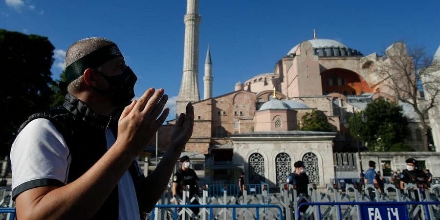 A Muslim man prays, following Turkey's Council of State's decision, outside the Byzantine-era Hagia Sophia in Istanbul