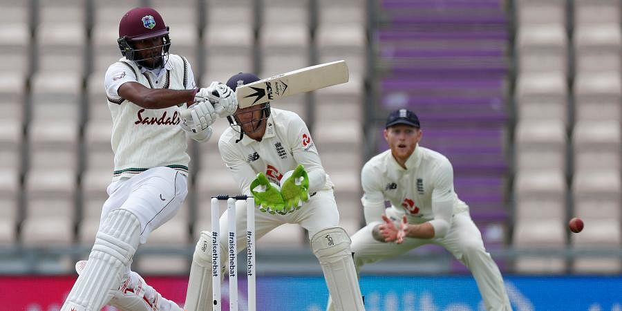 West Indies' Kraigg Brathwaite, left, plays a shot during the third day of the first cricket Test match between England and West Indies, at the Ageas Bowl in Southampton.