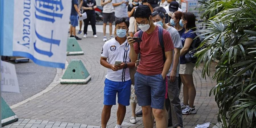 People wearing face masks queue up to vote in Hong Kong Saturday, July 11, 2020, in an unofficial 'primary' for pro-democracy candidates ahead of legislative elections in September.