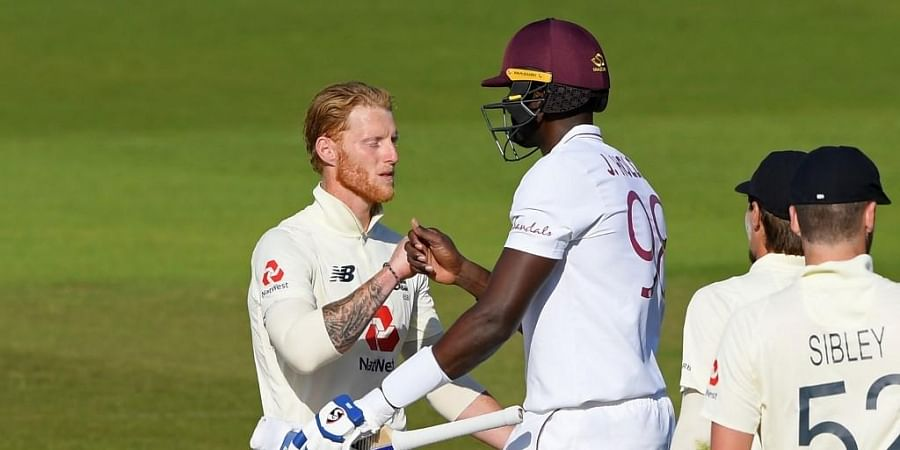 England's Ben Stokes (L) congratulates West Indies' Jason Holder (C) after West Indies win the test match on the fifth day of the first Test cricket match. (Photo | AFP)