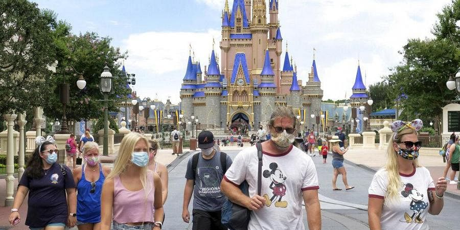 Guests wear masks as required to attend the official reopening day of the Magic Kingdom at Walt Disney World in Lake Buena Vista, Fla., Saturday, July 11, 2020.