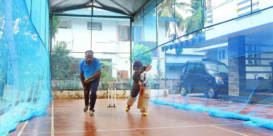 AR Madhavan along with his coach Veerendrakumar practicing cricket at his home near Kuthiravattam in Kozhikode