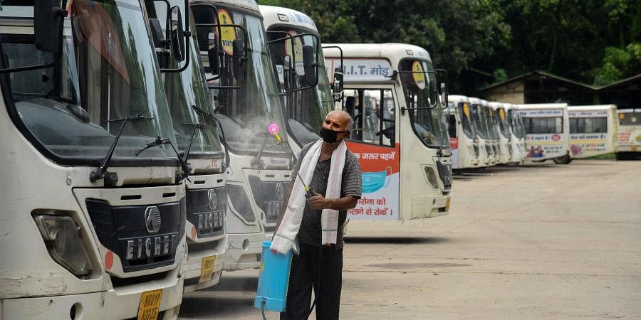 A worker sprays disinfectant on the buses parked at a depot during the total lockdown imposed to curb the spread of novel coronavirus in Patna Tuesday July 14 2020.